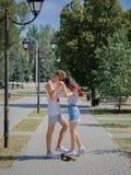Un couple mignon des ados datant en parc, montant sur un longboard sur un fond brouillé naturel Images stock