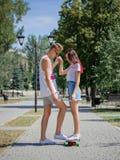 Un couple mignon des ados datant en parc, montant sur un longboard sur un fond brouillé naturel Photo stock