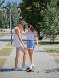 Un couple mignon des ados datant en parc, montant sur un longboard sur un fond brouillé naturel Photos stock