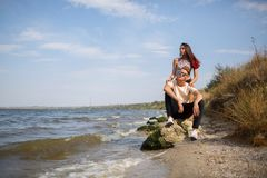 Un couple mignon des ados datant sur une rive, une belle fille et un camarade une date sur un fond brouillé naturel Image libre de droits