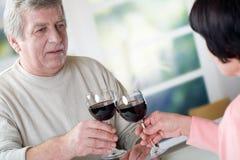 Un couple mûr heureux célébrant leurs années ainsi que le rouge Image libre de droits