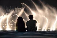 Un couple observant l'exposition de l'eau et de lumière du fountai de mail de Dubaï Photos stock