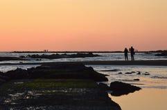 Un couple photographiant le spectacle naturel du coucher du soleil Images libres de droits