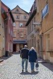 Un couple plus âgé dans l'amour marche le long d'une vieille rue allemande de pavé rond Photographie stock