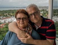 Un couple plus âgé dans les étreintes se tient sur le balcon de leur maison Idylle de famille, amour après des années Image libre de droits