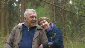 Un couple plus âgé et beau se reposant dans un bois, sur un bois scié Ils tendrement parlent, étreignent, dans le regard d'amour  clips vidéos