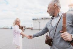 Un couple plus âgé marche autour de la place Une femme tient un homme par la main et mène Photographie stock libre de droits