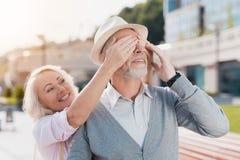 Un couple plus âgé marche dans la place La femme a approché l'homme par derrière et couvert ses yeux Image libre de droits
