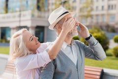 Un couple plus âgé marche dans la place La femme a approché l'homme par derrière et couvert ses yeux Image stock