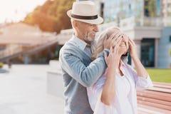 Un couple plus âgé marche dans la place L'homme a approché la femme par derrière et fermée ses yeux Image stock