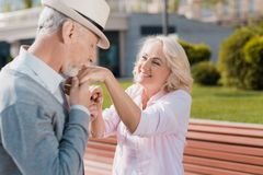 Un couple plus âgé marche dans la place L'homme embrasse la main du ` s de femme Elle sourit Image stock