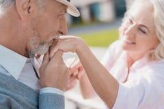 Un couple plus âgé marche dans la place L'homme embrasse la main du ` s de femme Elle sourit Photos libres de droits