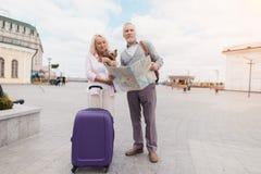 Un couple plus âgé marche le long du remblai avec leur petit chien Ils vont porter un sac pourpre de voyage Photographie stock libre de droits