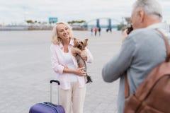 Un couple plus âgé marche Une femme pose avec un chien dans des ses bras, un homme prend des photos de elle sur un appareil-photo Photos libres de droits