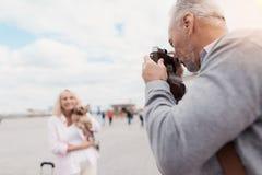 Un couple plus âgé marche Une femme pose avec un chien dans des ses bras, un homme prend des photos de elle sur un appareil-photo Photo libre de droits