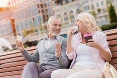 Un couple plus âgé repose se reposer sur un banc dans la place Ils mangent des hamburgers et boivent du café Photo stock