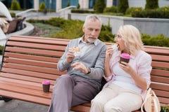 Un couple plus âgé repose se reposer sur un banc dans la place Ils mangent des hamburgers et boivent du café Photo libre de droits