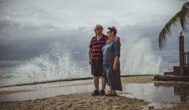 Un couple plus âgé se tient sur la plage et observer comme tempête de approche dans les vagues Photographie stock