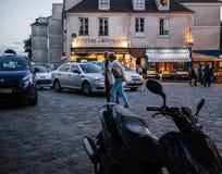 Un couple plus ancien flâne à travers la place de Montmartre entre les motos et les taxis dans la soirée Photographie stock libre de droits