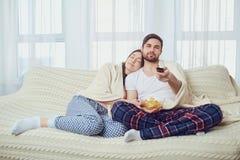Un couple regardant la TV se reposer sur le divan dans la chambre image stock