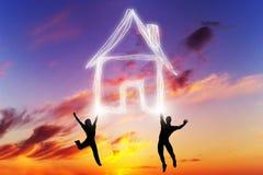 Un couple saute et fait un symbole de maison de lumière Photos libres de droits