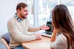 Un couple se reposant dans un café riant gaiement, un type se dirige à l'ordinateur portable Image libre de droits