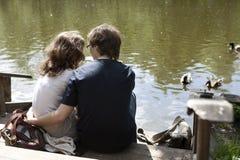 Un couple se reposant près du fleuve Photographie stock