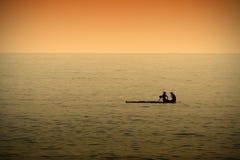 Un couple se reposant tout en paddleboarding en mer calme au temps de coucher du soleil Image stock
