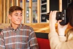 Un couple se repose dans un café La fille prend des photos d'un type qui grimace un appareil-photo inside Photo libre de droits