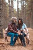 Un couple se repose dans la forêt, couverte de couverture, regardant l'un l'autre avec un sourire Photo stock