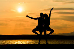 Un couple se tenant au coucher du soleil par une mer Photographie stock libre de droits