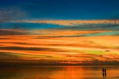 Un couple se tenant dans l'océan au coucher du soleil Photos stock