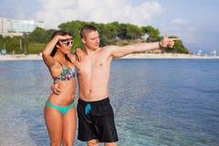 Un couple se tenant sur la côte de la mer et ayant l'amusement Images libres de droits