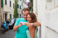Un couple se tenant sur la rue et à l'aide du smartphone Images libres de droits