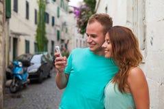 Un couple se tenant sur la rue et à l'aide du smartphone Photo stock