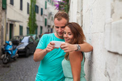Un couple se tenant sur la rue et à l'aide du smartphone Images stock