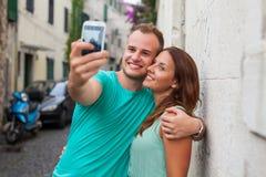 Un couple se tenant sur la rue et à l'aide du smartphone Photos stock