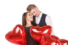 Un couple se tient parmi les boules sous forme de coeur et embrasse doucement D'isolement sur le blanc Image stock