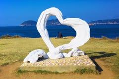 Un couple situé dans l'objet du coeur au cap Hado dans Karatsu, Japon Photo libre de droits