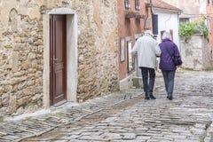 Un couple supérieur marchant sur les rues d'une ville antique photographie stock libre de droits
