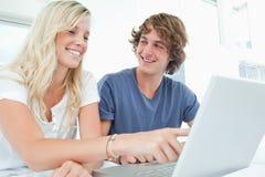 Un couple utilise un ordinateur portable avec un homme regardant la femme Photos stock