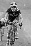 Un coureur féminin de cycloross escalade la côte boueuse Photographie stock libre de droits