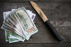 Un couteau et certains ont éventé la pose d'argent liquide image stock