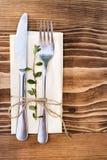 Un couteau et une fourchette sur une serviette sur un brun, table en bois Vue supérieure Photo stock