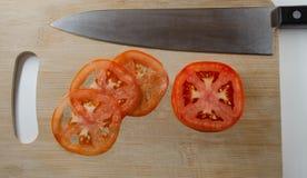 Un couteau pointu et trois tranches très minces d'une tomate photo stock