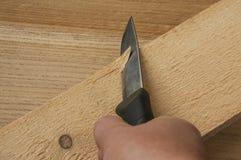 Un couteau pointu, une planche à découper en bois Images stock