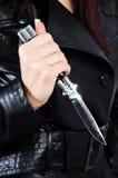 Un couteau s'est retenu par un femme dans le noir Images stock