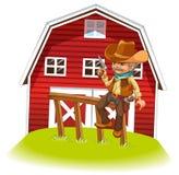 Un cowboy che tiene una pistola che si siede su un legno davanti al barnhou Fotografie Stock