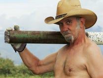 Un cowboy sans chemise Shoulders une barrière Post Driver Photo stock