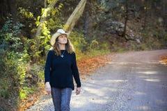 Un cowgirl cammina Forest Road nella caduta Fotografia Stock Libera da Diritti